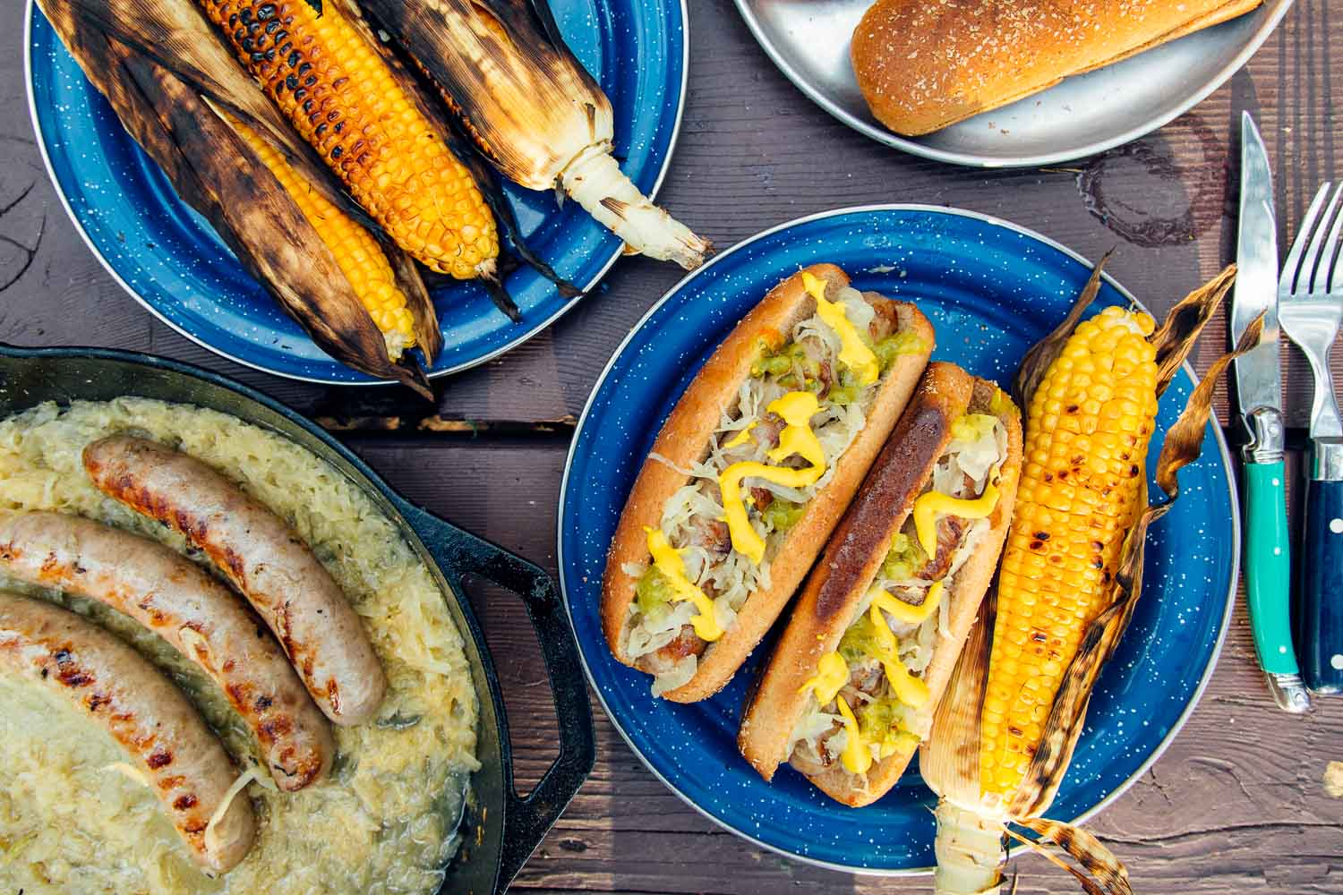 Overhead view of a plate with grilled beer brats, sauerkraut, and grilled corn