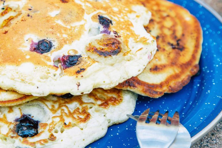 A short stack of blueberry pancakes on a blue plate