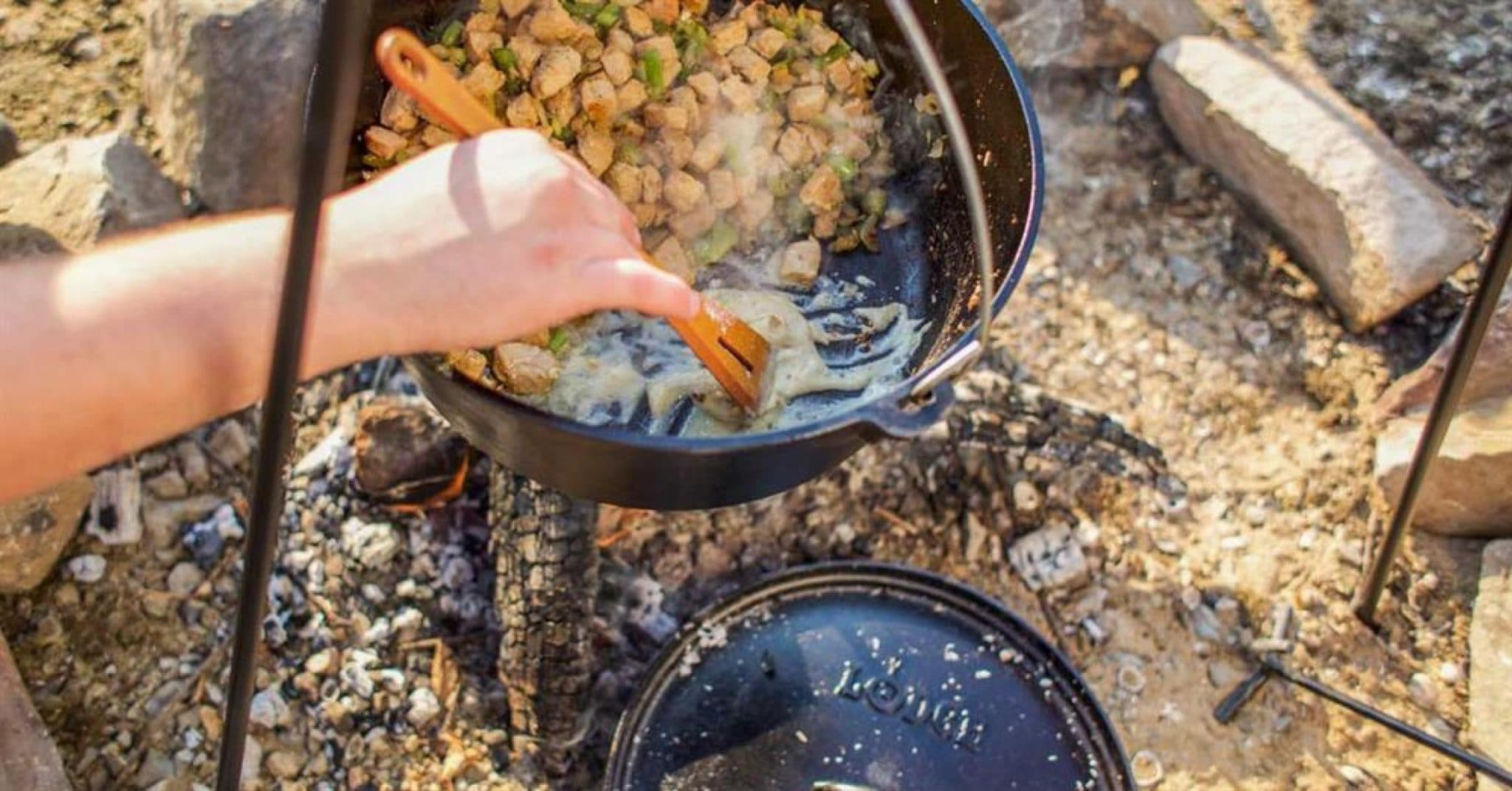 Stirring chile verde in a Dutch oven hanging over a campfire