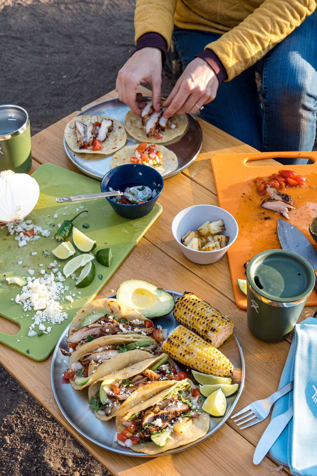 A table scene with a plate of tacos in the foreground and Megan's hands assembling tacos on a second plate