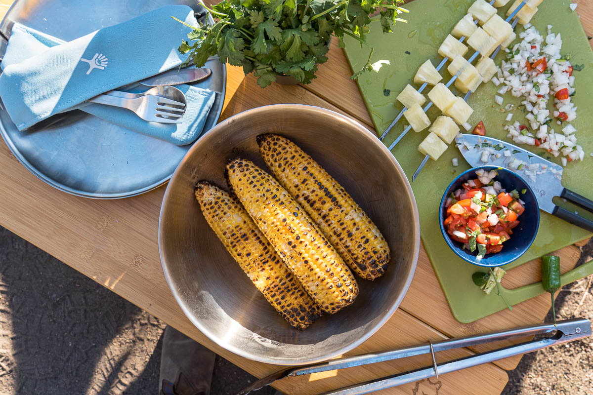 Three ears of grilled corn in a large bowl surrounded by other taco side dishes.