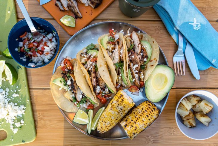 Four tacos arranged on a plate with grilled corn on the cob and hal an avocado