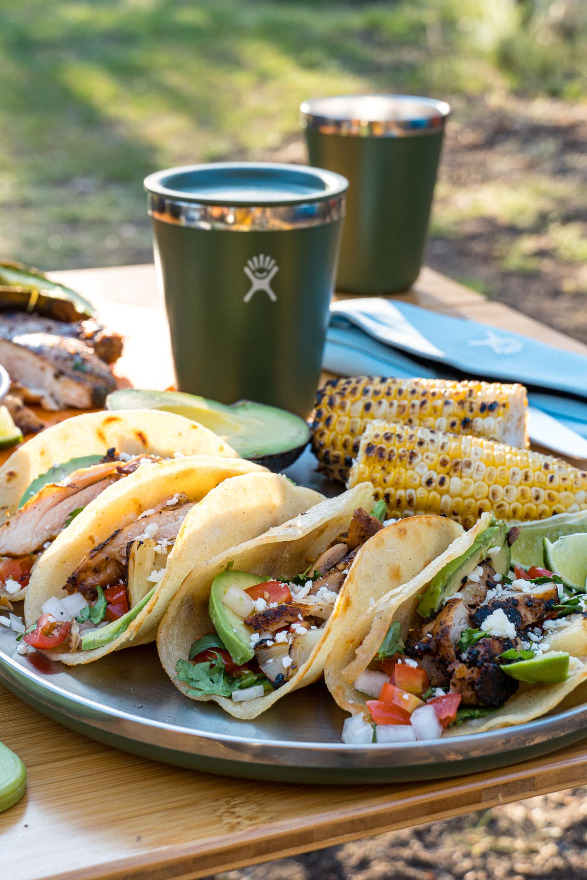 Four grilled chicken tacos on a plate with a green drinking glass in the background