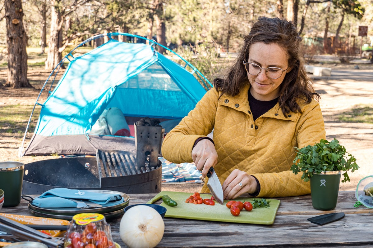 Megan chopping ingredients for tacos with a camp scene in the background