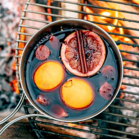 Wine with oranges and a cinnamon stick in a pot over a campfire