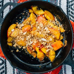 Sliced peaches topped with granola in a skillet