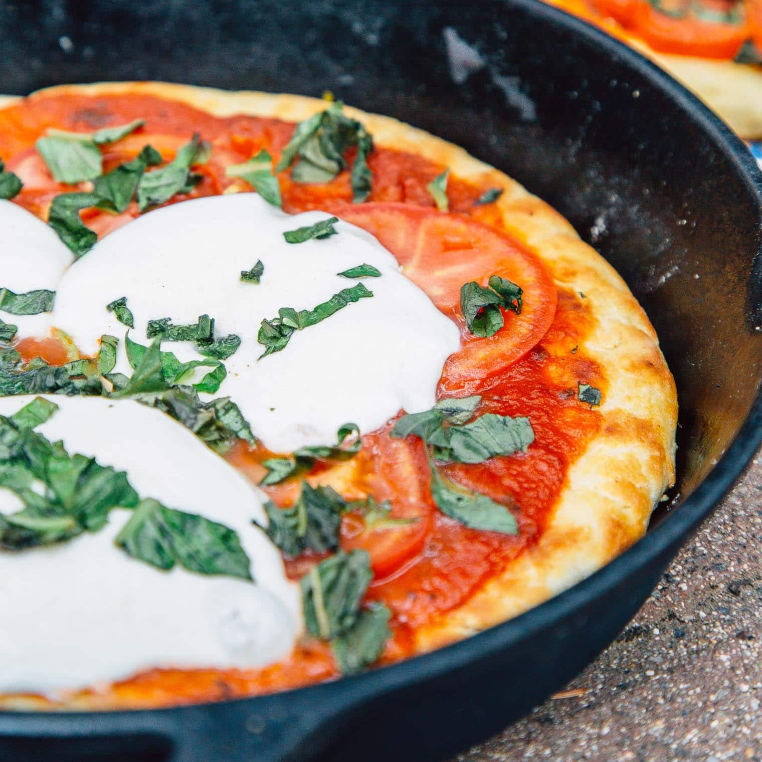 Pizza topped with mozzarella cheese slices and basil in a cast iron skillet