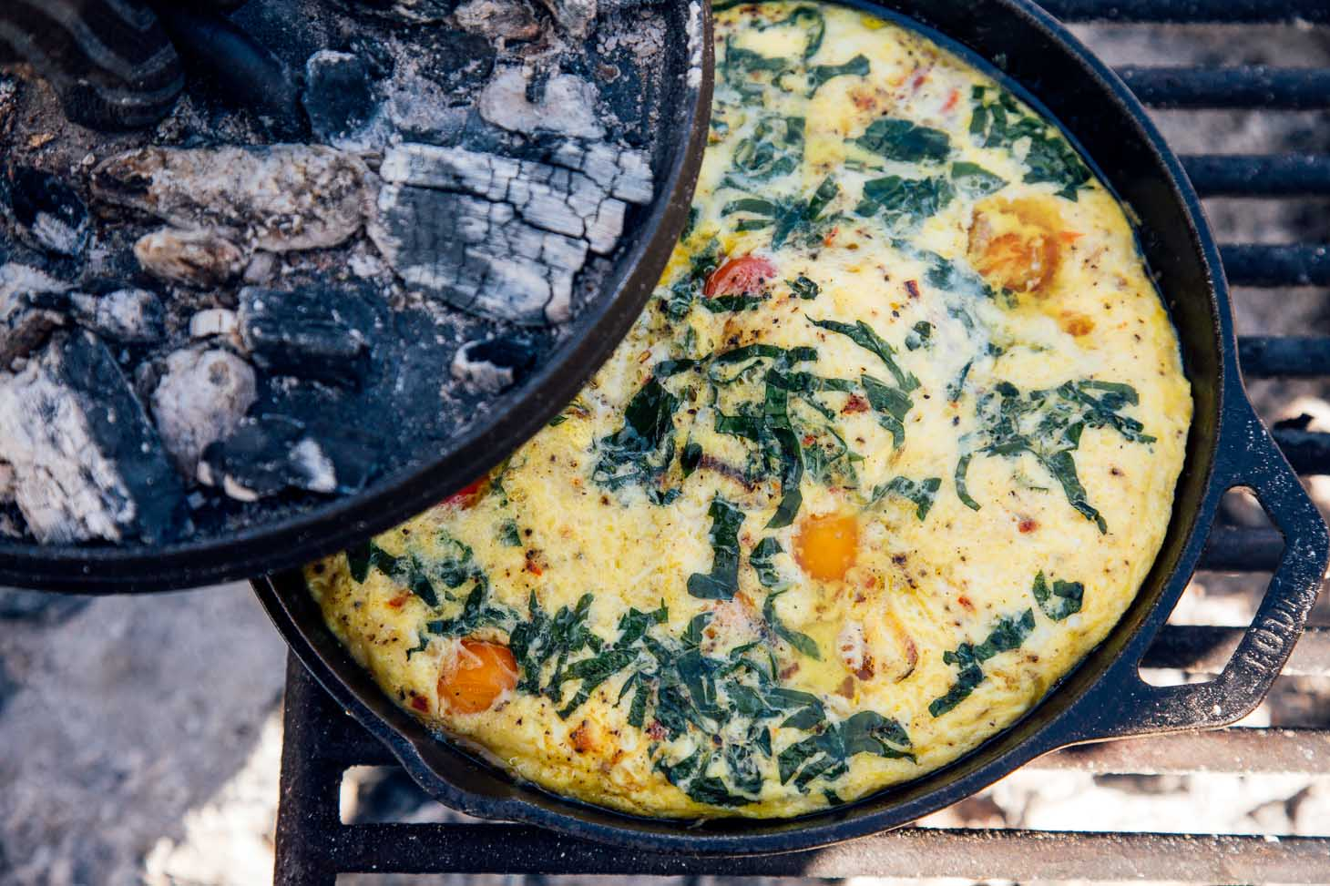Lid to a cast iron skillet being removed to reveal a vegetable frittata.