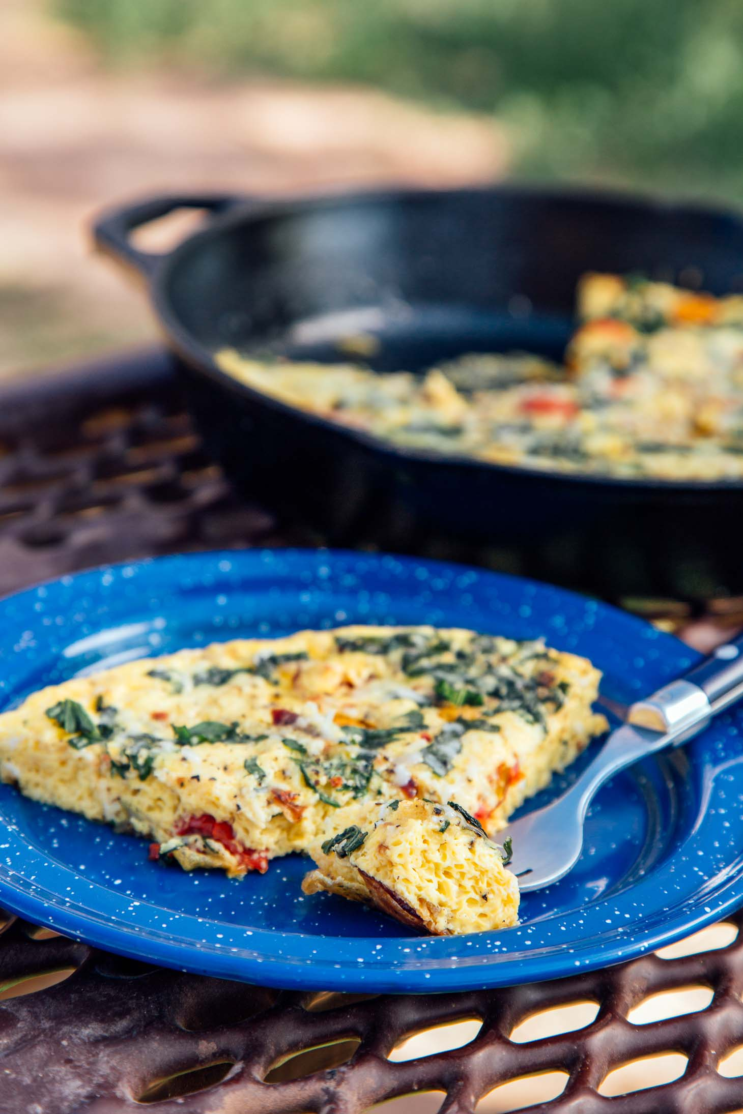 A slice of vegetable frittata on a blue plate on a camping table.