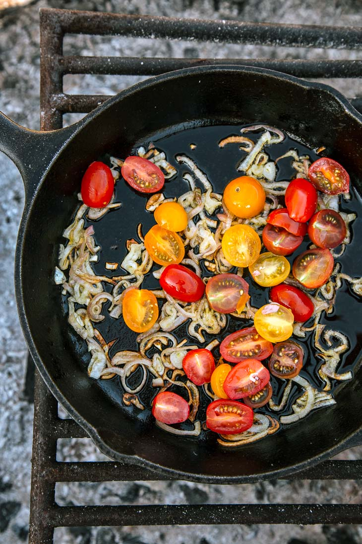 Cherry tomatoes and shallots in a cast iron skillet over a campfire