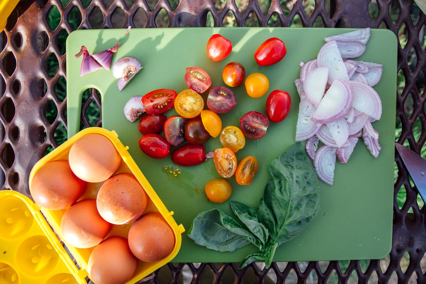 Ingredients for frittata: eggs, tomatoes, shallots, garlic, basil laid out on a cutting board.