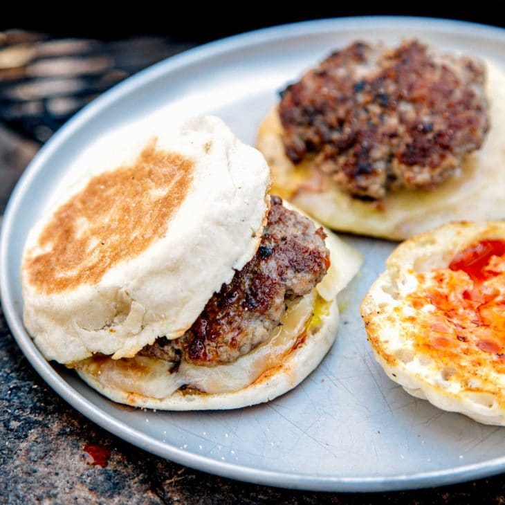 Two sausage patties on english muffins on a silver plate