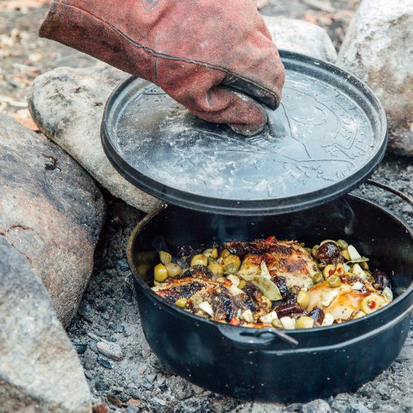 Michael lifting the lid off of a Dutch oven sitting in a fire pit.
