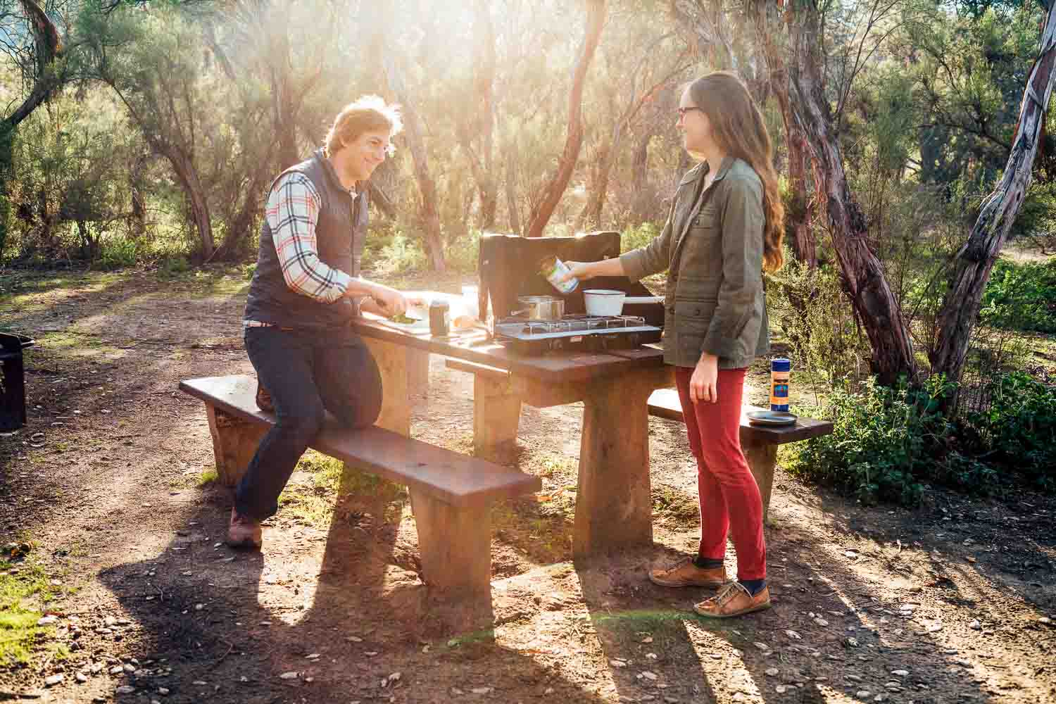 Man and woman at a campsite cooking a meal on a camping stove.