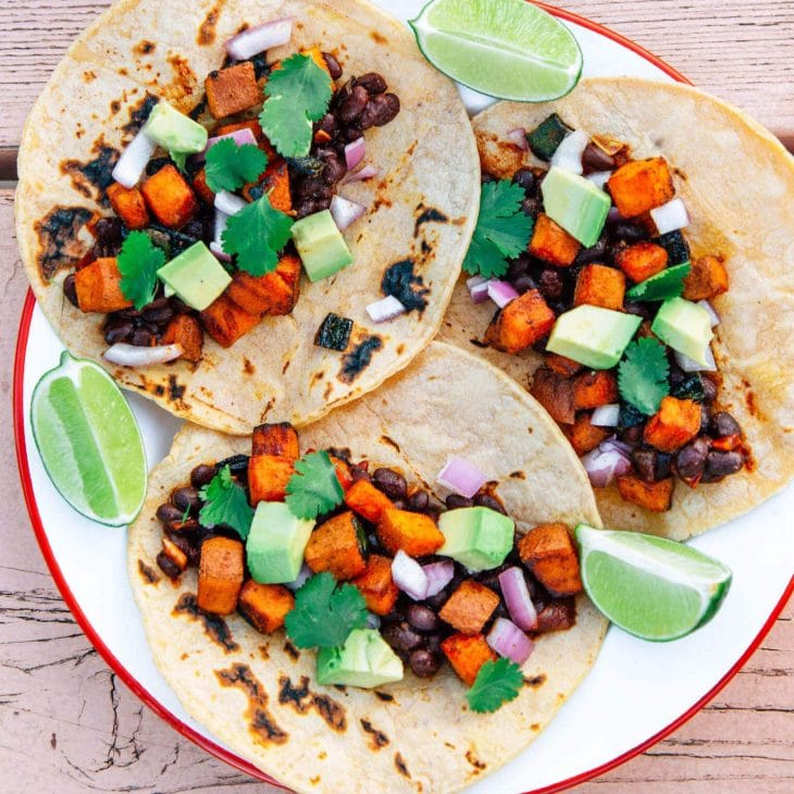 Three tacos on a plate filled with black beans, sweet potato, and avocado