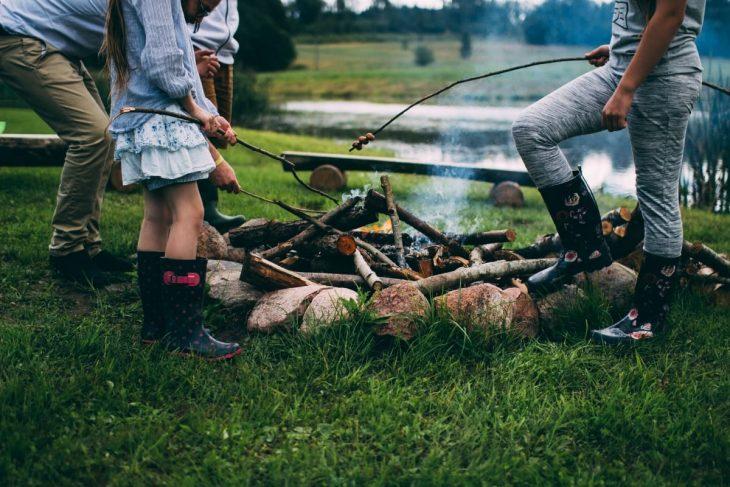 Family roasting marshmallows around a campfire