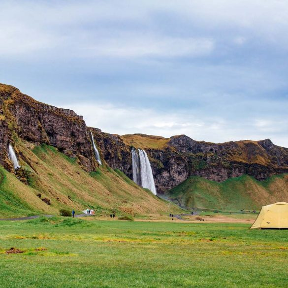 A yellow tent in a field with the Seljalandsfoss waterfall in the backgroundthe