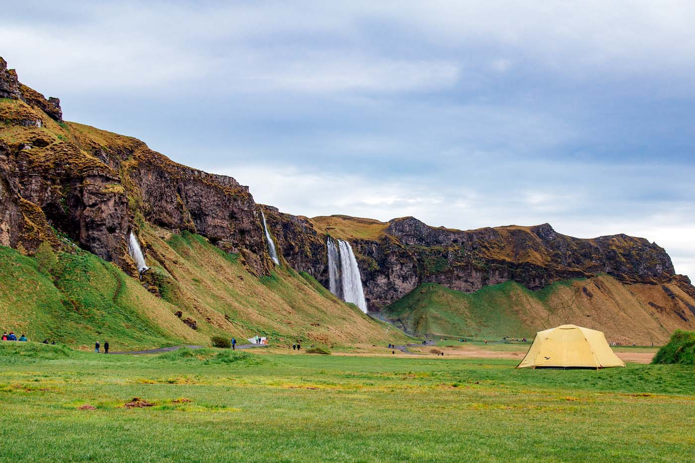 A yellow tent in a field with the Seljalandsfoss waterfall in the background