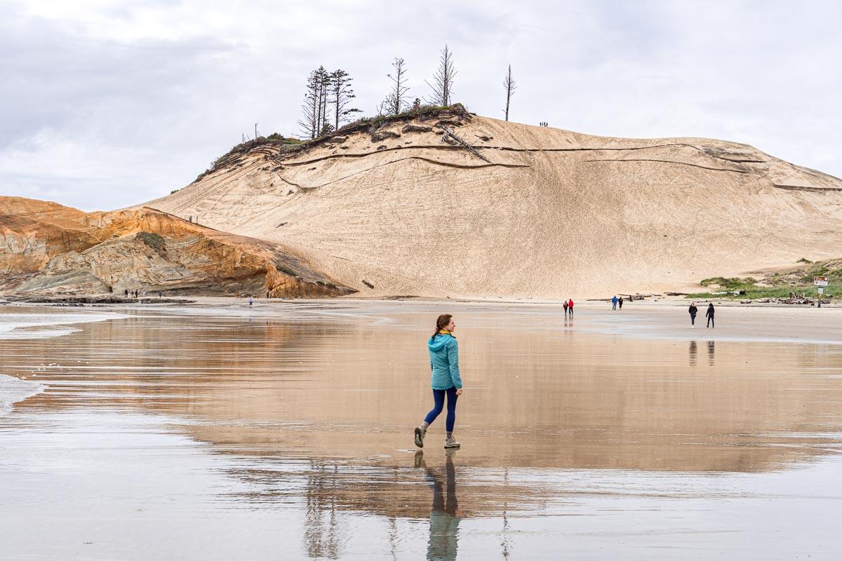 Megan walking on a beach towards a large sand dune.