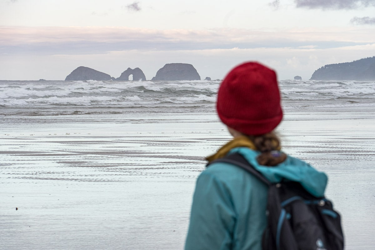 Megan stands on a beach and looks out at rock formations.