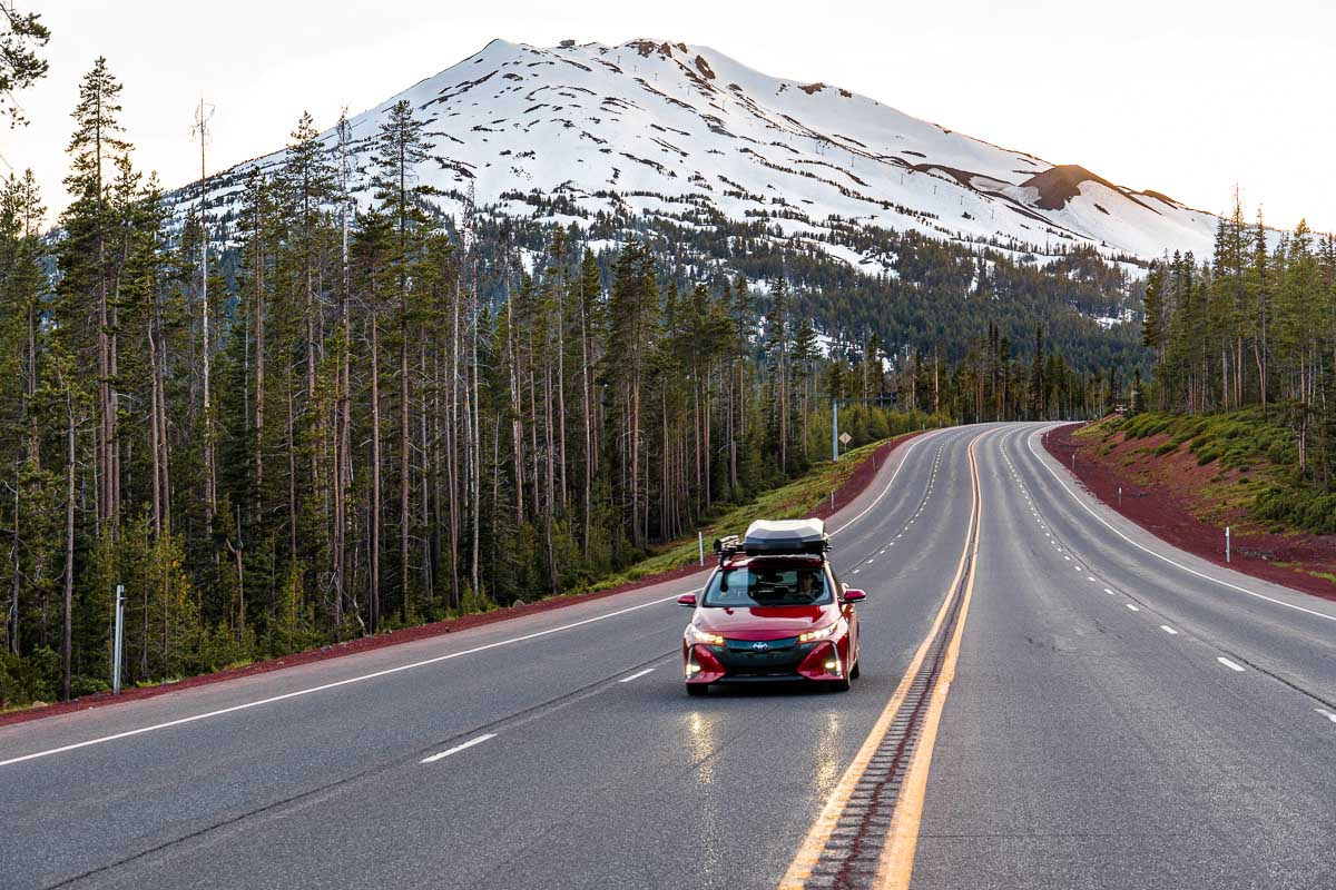 A red Prius Prime driving down a road with a snowcapped mountain in the distance.