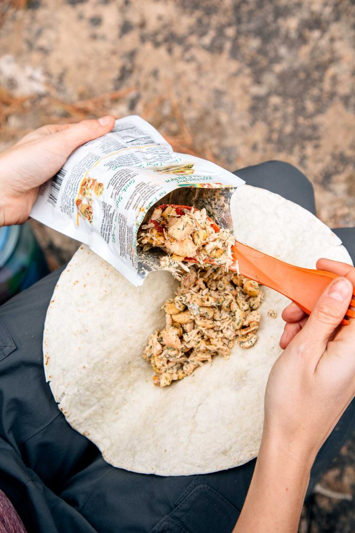 Filling a tortilla with cashew chicken salad