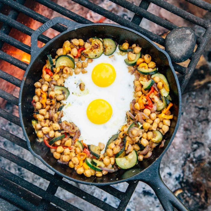 Chickpeas, vegetables, and two eggs in a skillet over a campfire.
