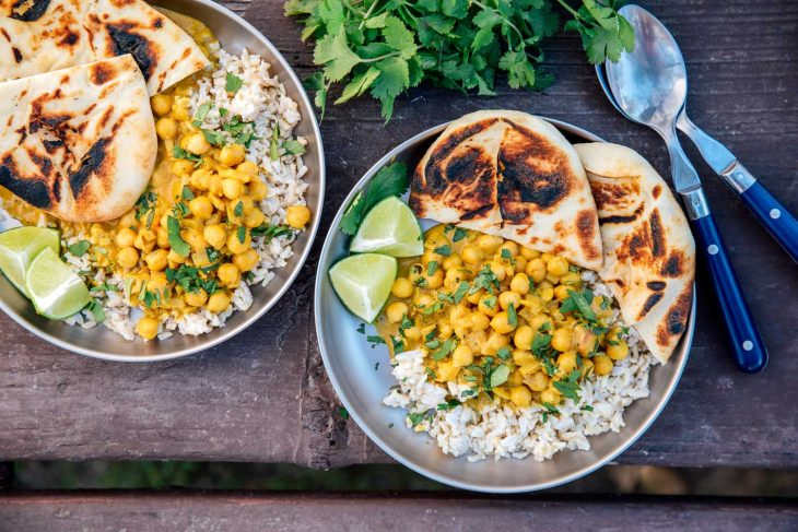 Two plates of coconut chickpea curry over rice on a camping table.