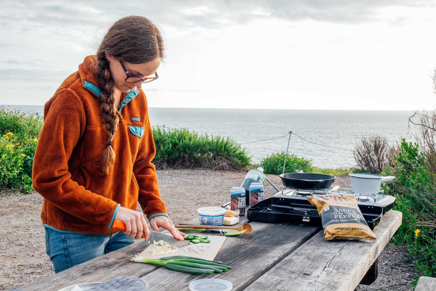 Woman chopping jalapeños at a campsite. A camping stove and other nacho ingredients are visible in the background.