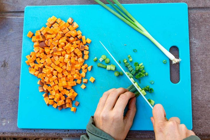 Megan chopping green onions and cubed sweet potatoes on a cutting board.