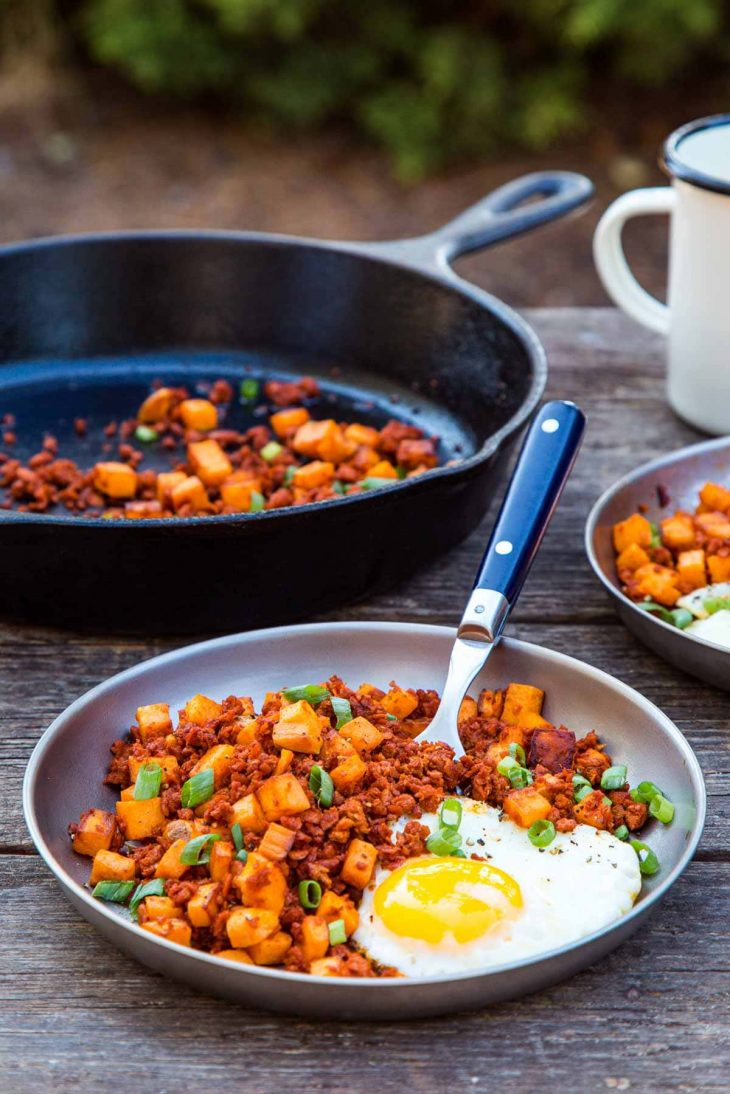 Sweet potato and chorizo hash with an egg on a plate.