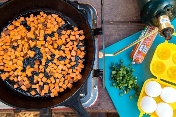 Sweet potatoes in a cast iron skillet with other ingredients to the side.