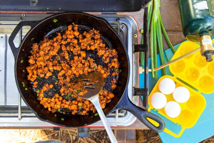 Browning chorizo with sweet potatoes in a cast iron skillet on a camp stove