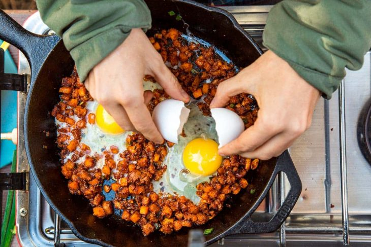 Megan cracking an egg into a skillet of sweet potato breakfast hash