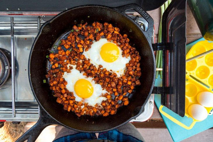 Two eggs in a cast iron skillet filled with chorizo and sweet potatoes