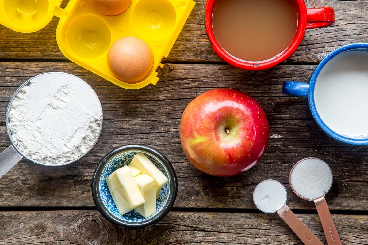 Ingredients for apple pancakes: flour, butter, apples, egg, milk, apple cider, sugar and baking soda.