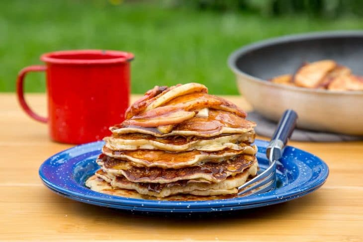 A stack of pancakes with cinnamon apple topping on a blue camping plate.