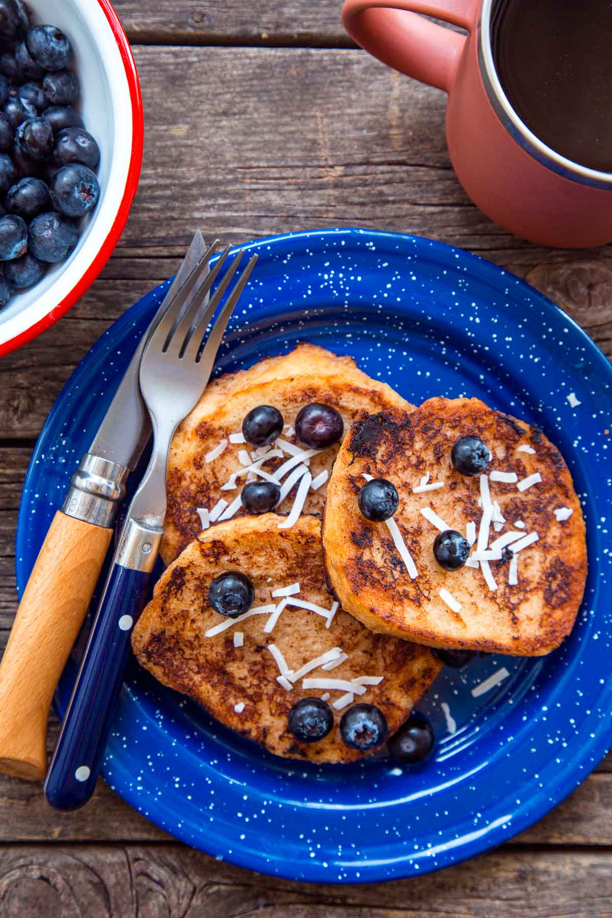 Three slices of French toast with blueberries on a blue plate