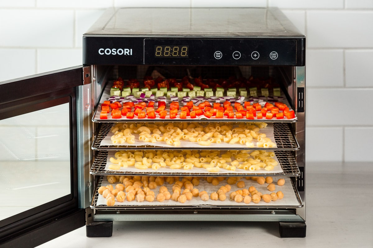 A dehydrator with the door open to show trays of food