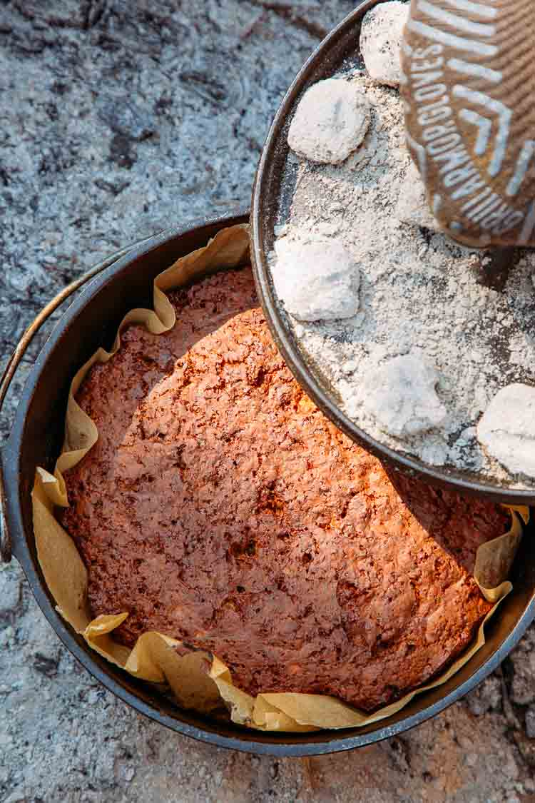 Removing the lid from a dutch oven to reveal baked banana bread
