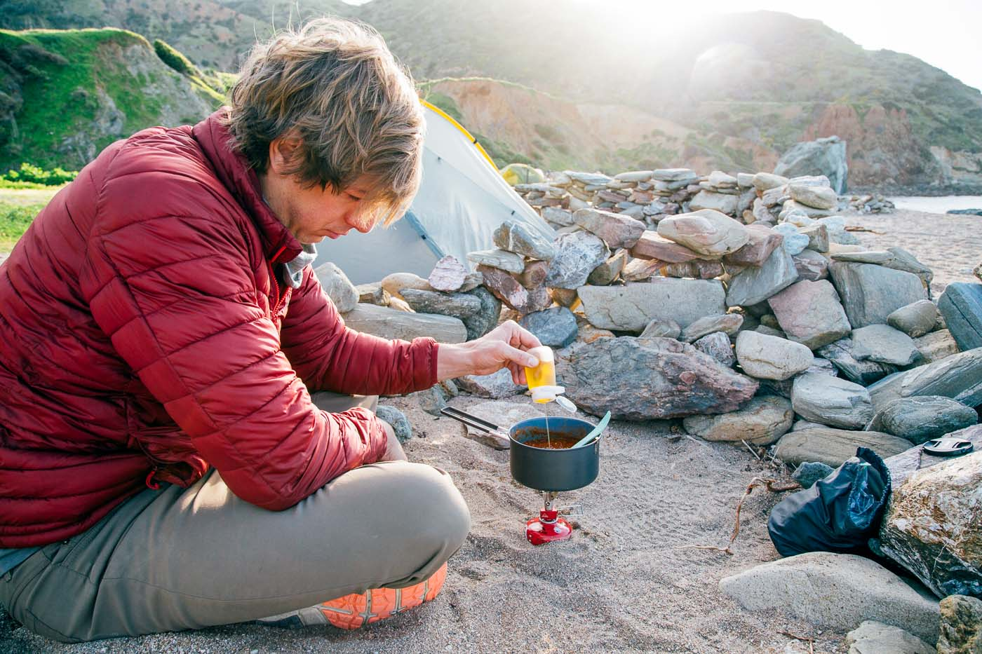 A man adding oil to a backpacking pot full of chili.