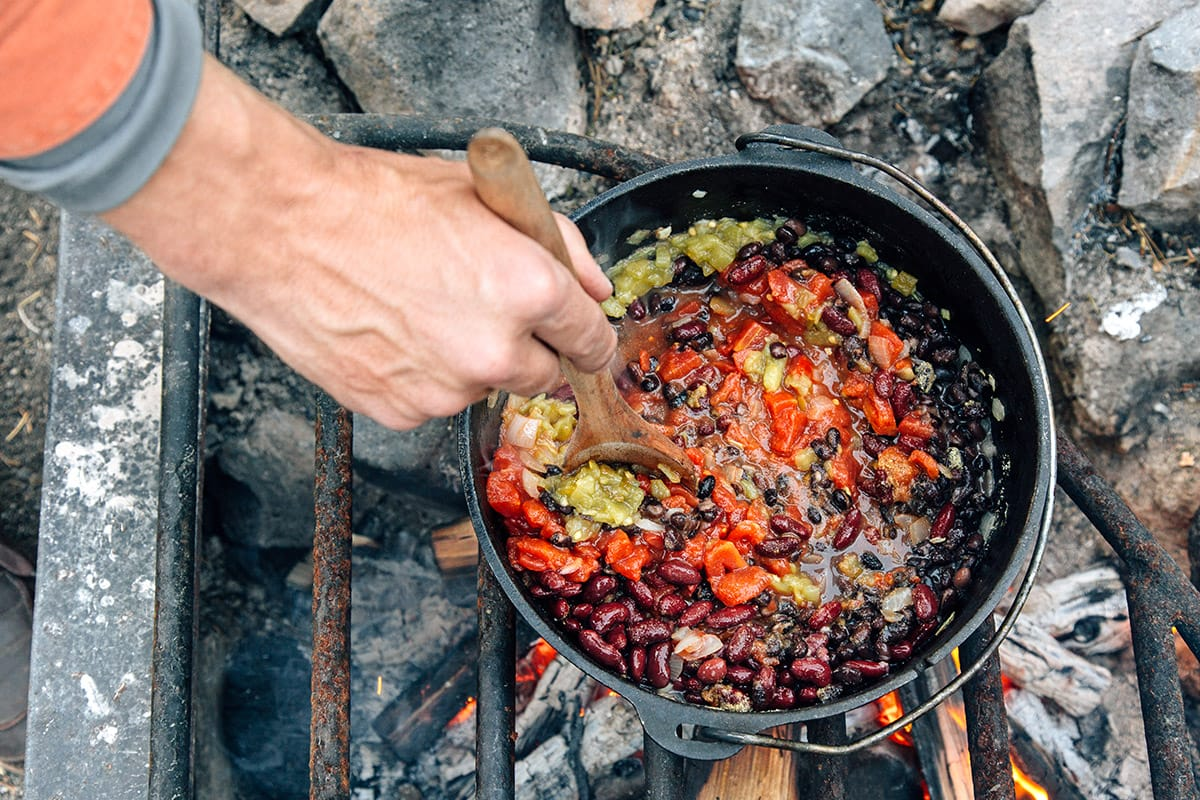 Michael stirring tomatoes, beans, and chilies in a Dutch oven over a campfire