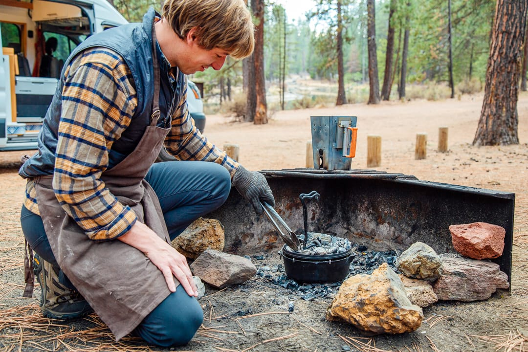 Michael using tongs to place charcoals on top of a camping dutch oven