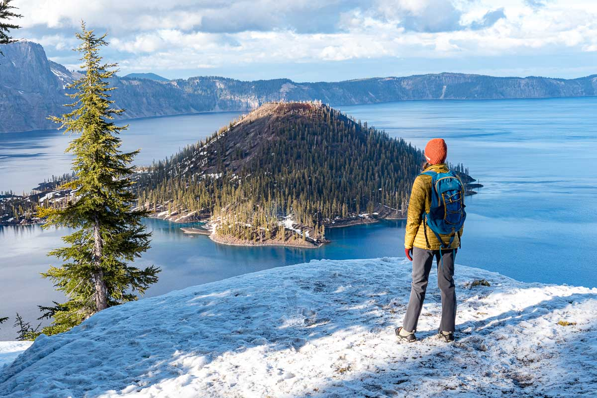 Megan standing on a snowy trail looking out at Wizard Island in Crater Lake