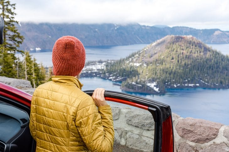 Megan stands next to a red car and looks out at Crater Lake