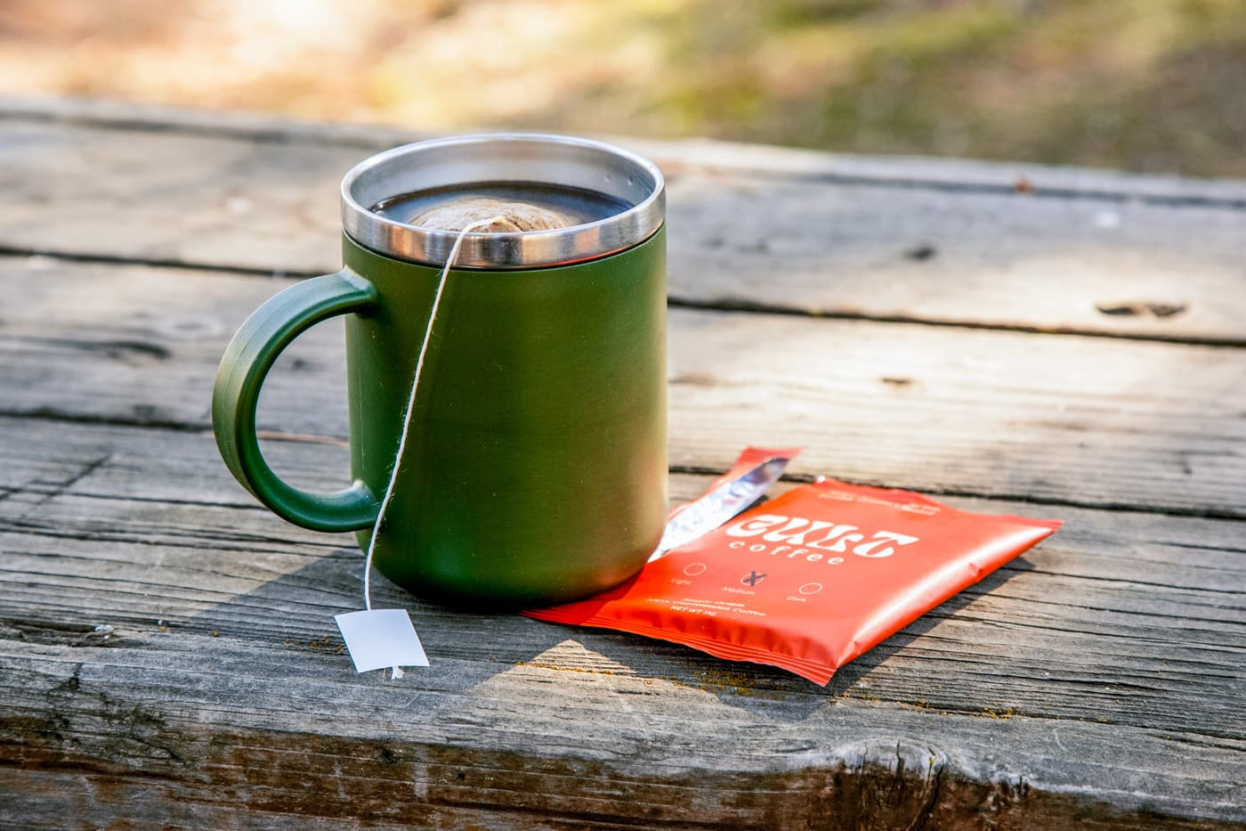 A green mug of coffee on a camping table