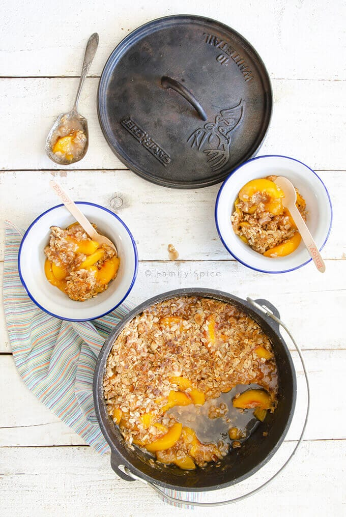 Peach crisp in a dutch oven with two white and blue bowls