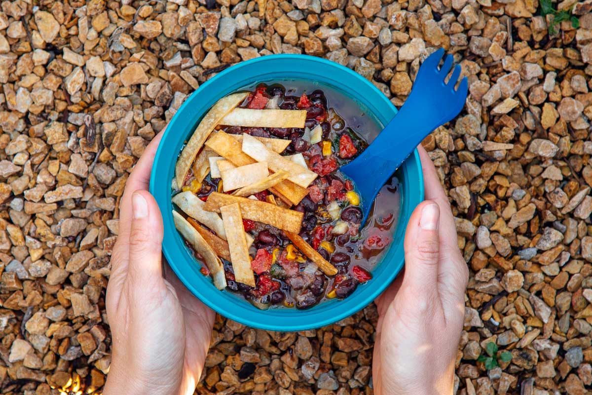 A bowl of tortilla soup on a natural background with hands