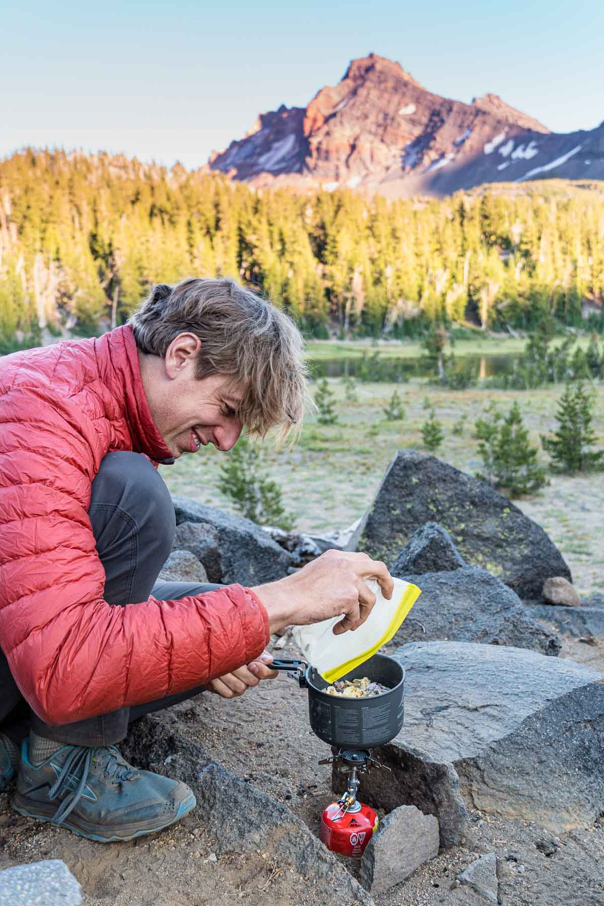 Michael andding food to a backpacking pot. There is a forest and mountain peak in the distance.