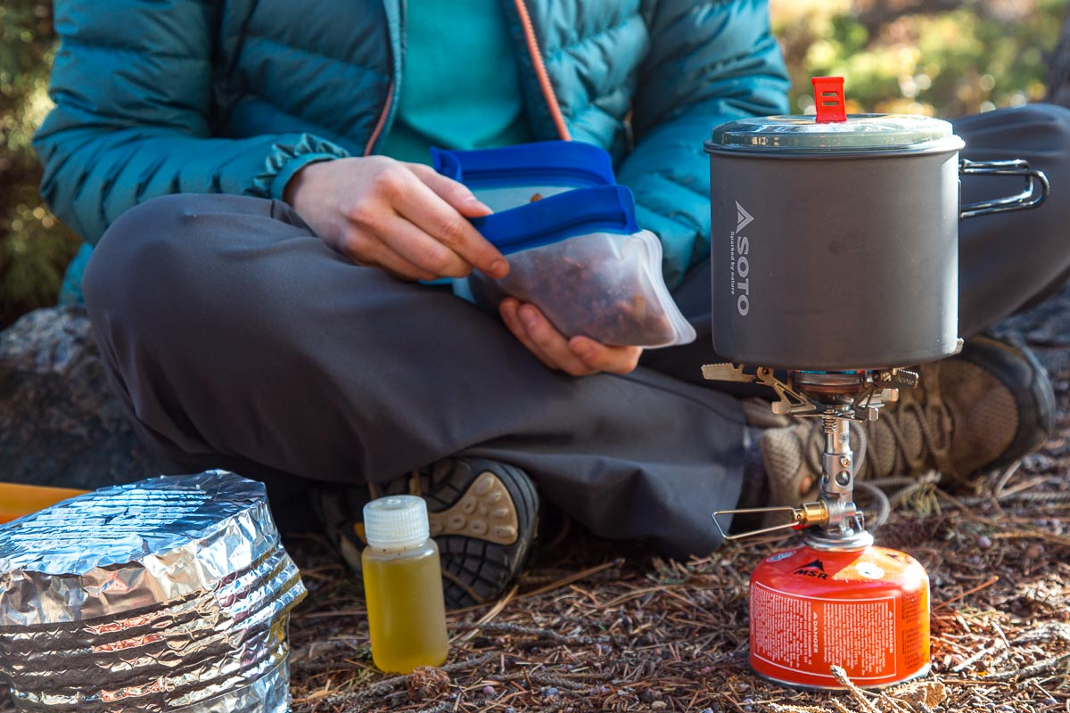 Megan holding a bag of backpacking food with a pot on a stove in the foreground